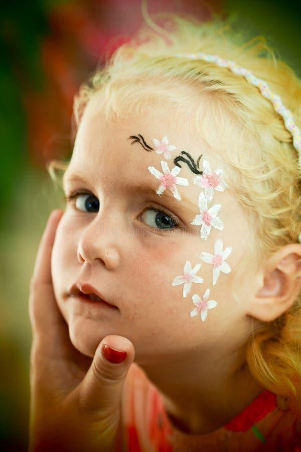 小的白肤金发的蓝眼睛的女孩面孔绘画 免版税图库摄影