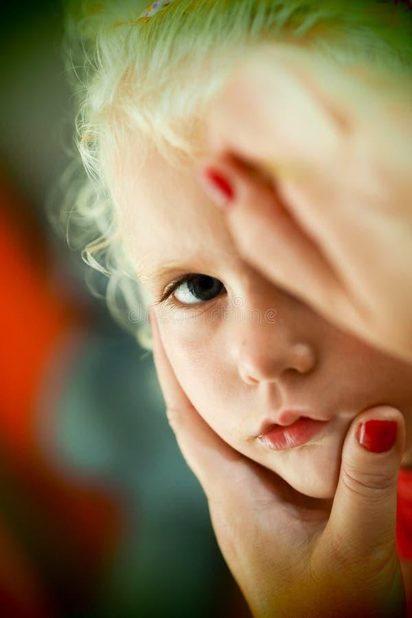 小的白肤金发的蓝眼睛的女孩面孔绘画 免版税库存图片
