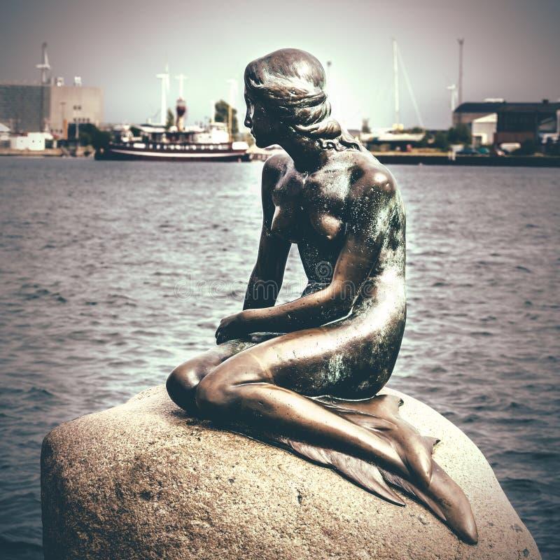小的美人鱼是一个古铜色雕象由Edvard Eriksen,描述美人鱼 雕塑在岩石被显示由watersid 库存图片
