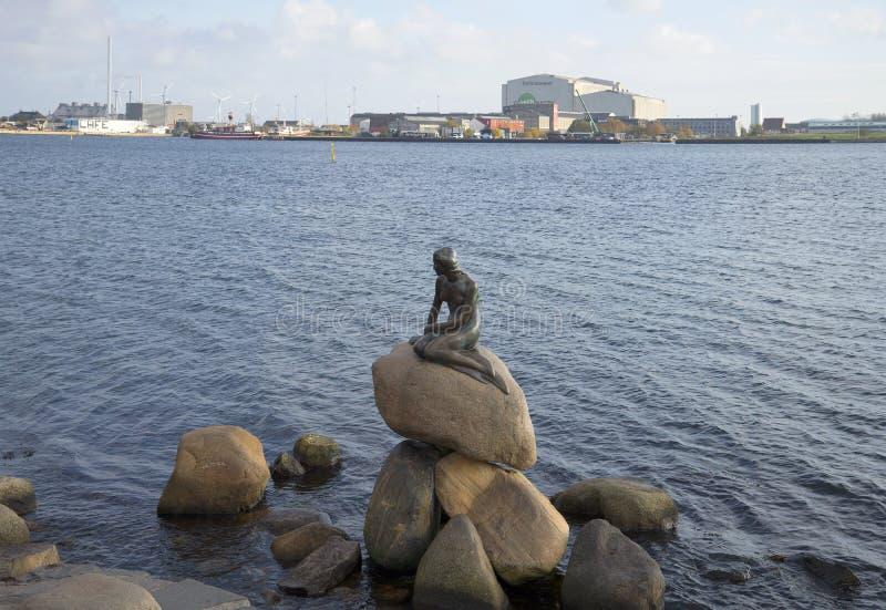 小的美人鱼的雕塑在港口江边的背景的 哥本哈根丹麦 免版税库存照片