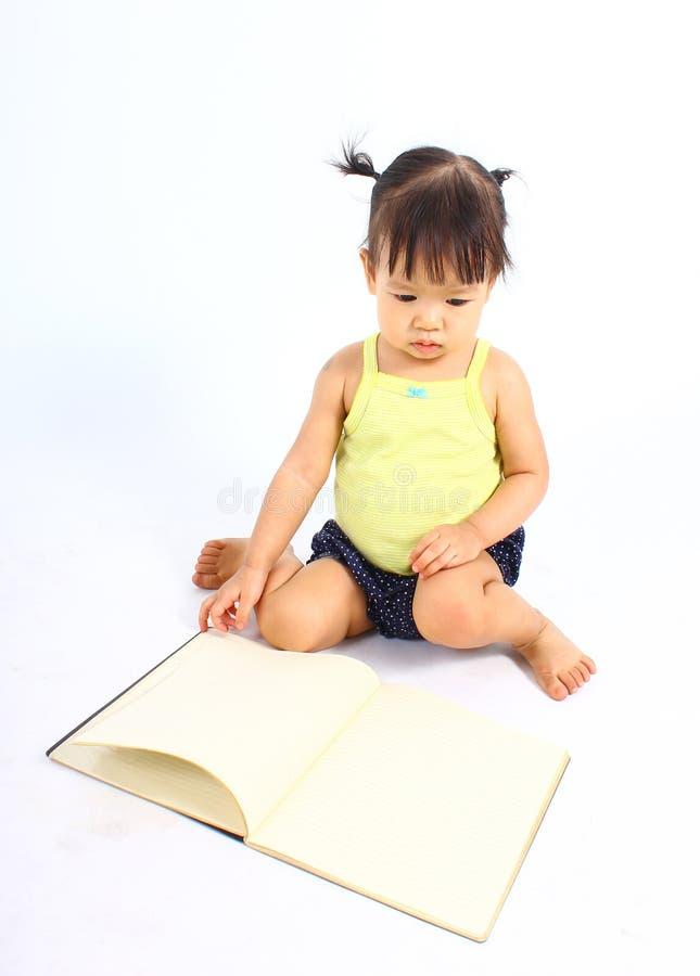小的逗人喜爱的女婴阅读书画象  免版税库存图片