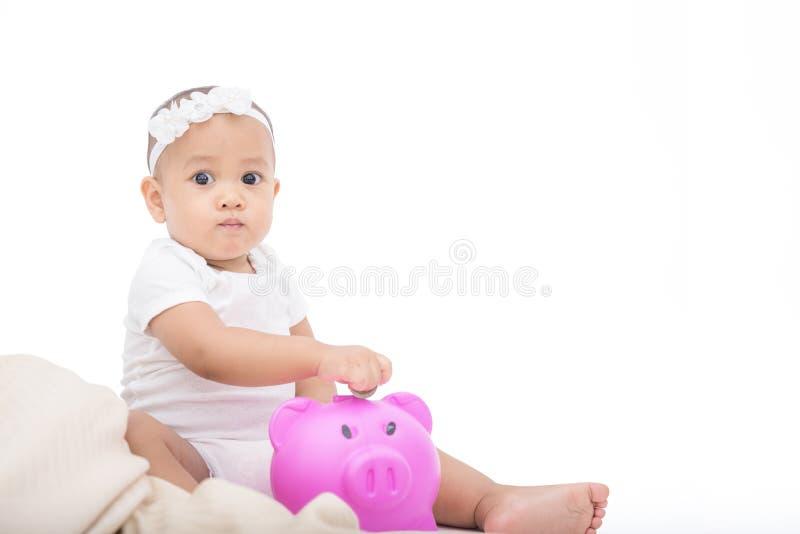 小的逗人喜爱的婴孩挽救金钱到教育的存钱罐里 免版税库存图片