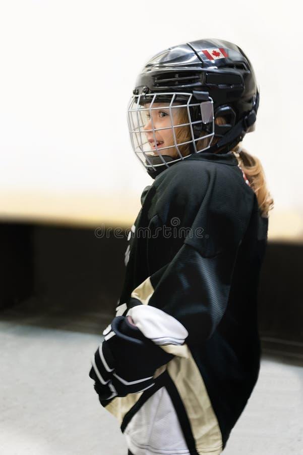 小的逗人喜爱的白肤金发的加拿大3年年纪女孩打在充分的曲棍球设备的曲棍球 库存照片
