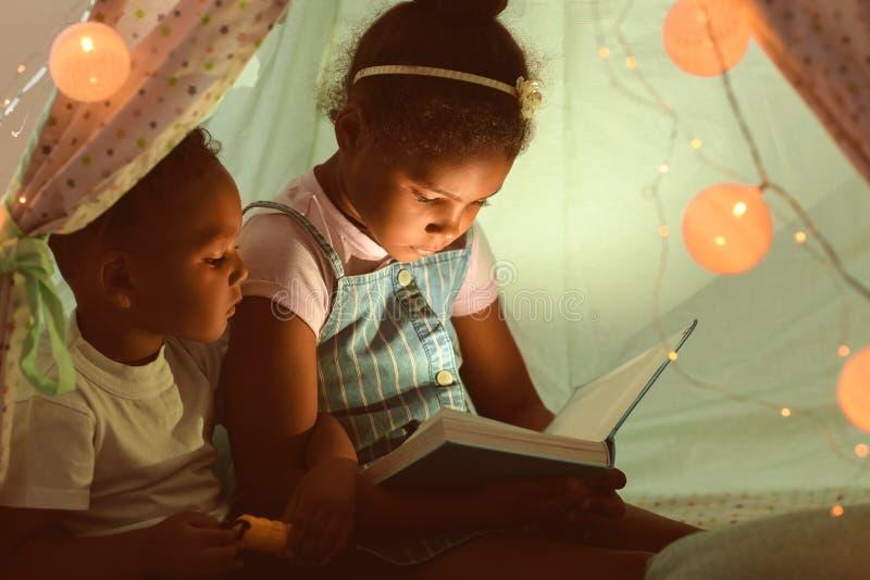 小的非裔美国人的儿童读书催眠故事在小屋 免版税库存图片