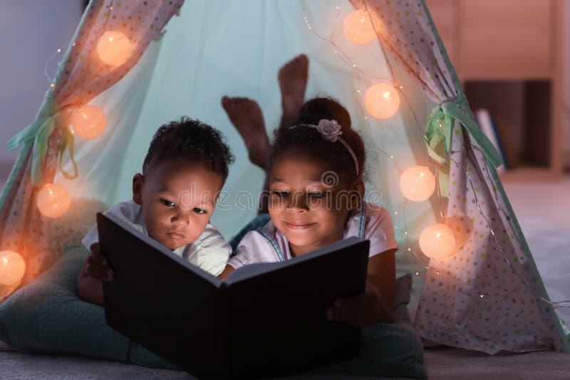 小的非裔美国人的儿童读书催眠故事在小屋 免版税图库摄影