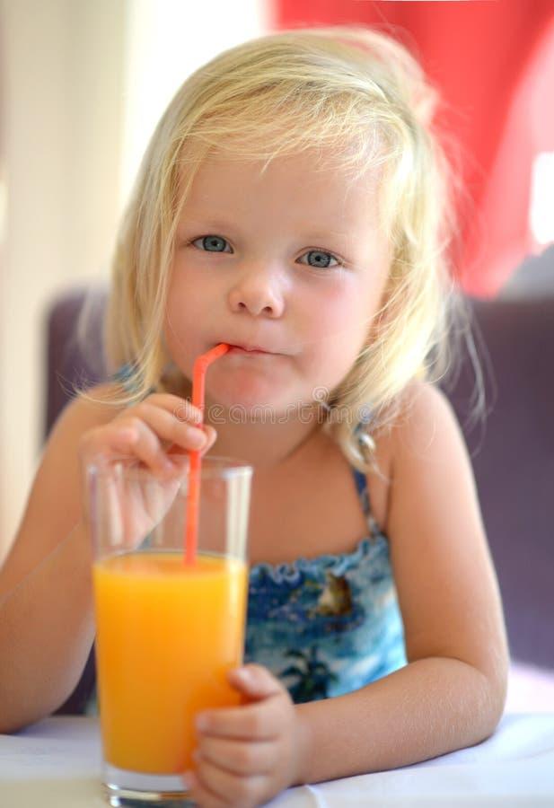 小的从高玻璃杯的女婴饮料橙汁与str 免版税图库摄影