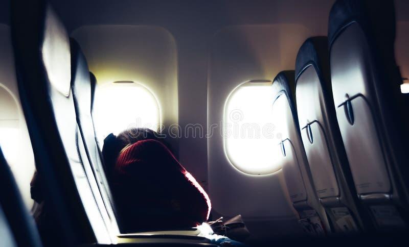 小睡在位子的疲乏的偶然不可能验明的千福年的白种人年轻女人,当旅行乘有明亮的时飞机 库存照片