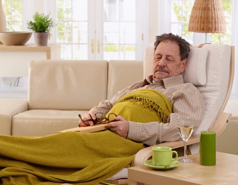 小睡在扶手椅子的老人 免版税库存图片