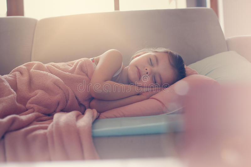 小睡在长沙发的小女孩 库存图片