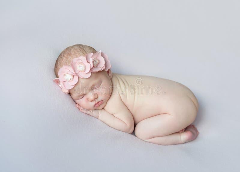 小睡在他的腹部的可爱的赤裸婴孩 免版税库存图片