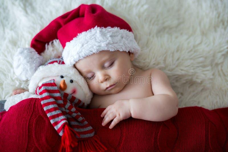 小睡觉的新出生的男婴,佩带的圣诞老人帽子 免版税库存照片
