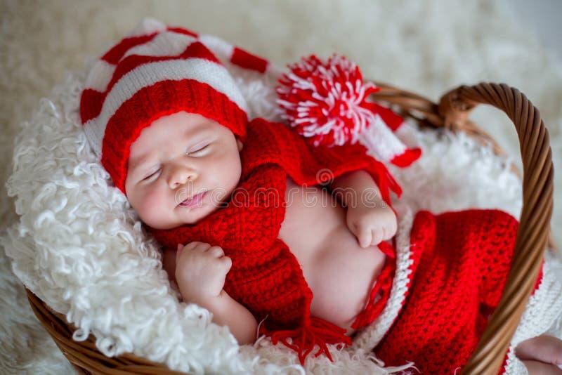 小睡觉的新出生的男婴,佩带的圣诞老人帽子 免版税图库摄影