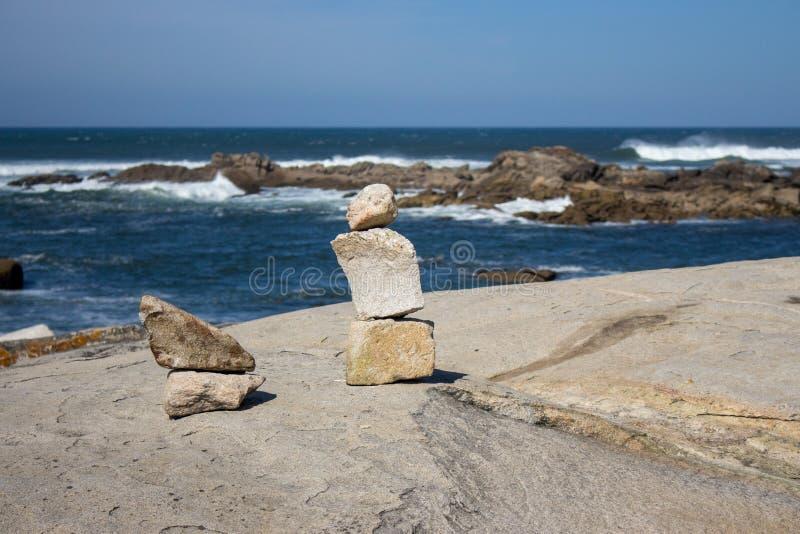 小石头塔在海洋海岸的与在背景的岩石 与石艺术的海景 平衡和和谐概念 免版税库存照片