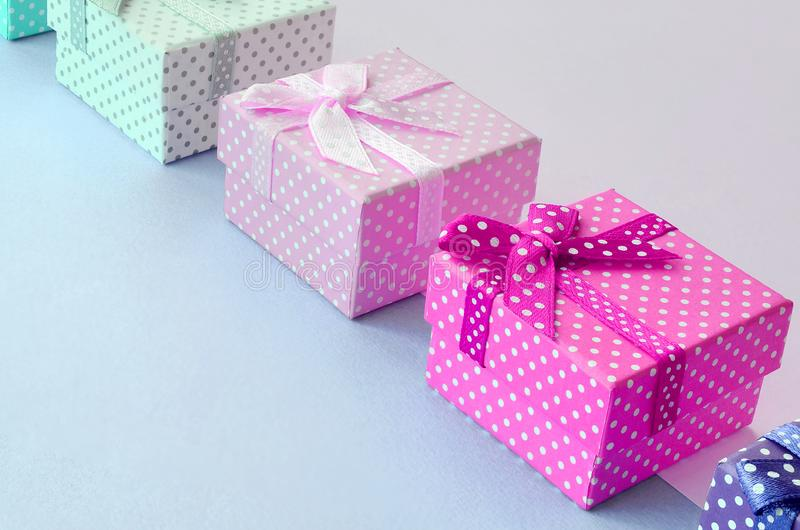 小礼物盒与丝带谎言的不同颜色在紫罗兰色和桃红色背景 库存图片
