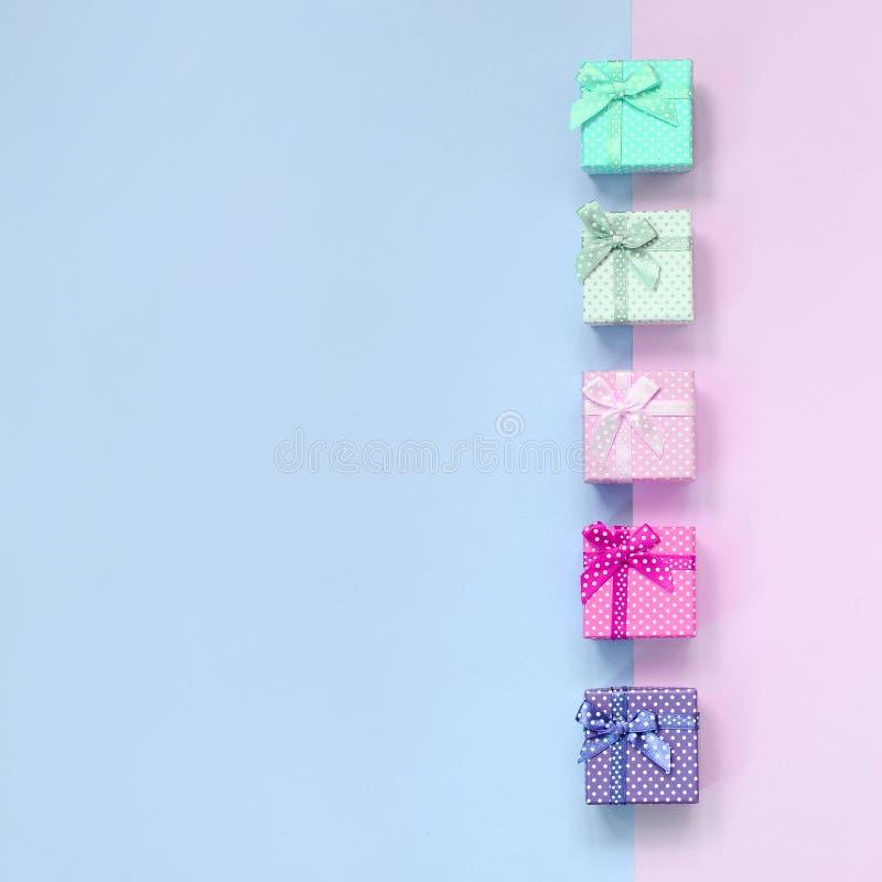 小礼物盒与丝带谎言的不同颜色在紫罗兰色和桃红色背景 库存照片