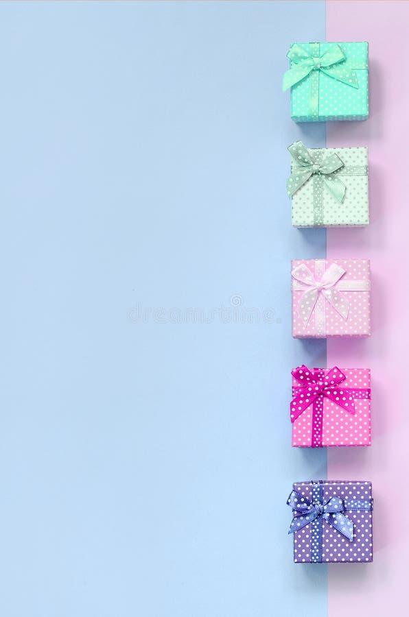 小礼物盒与丝带谎言的不同颜色在紫罗兰色和桃红色背景 免版税库存照片