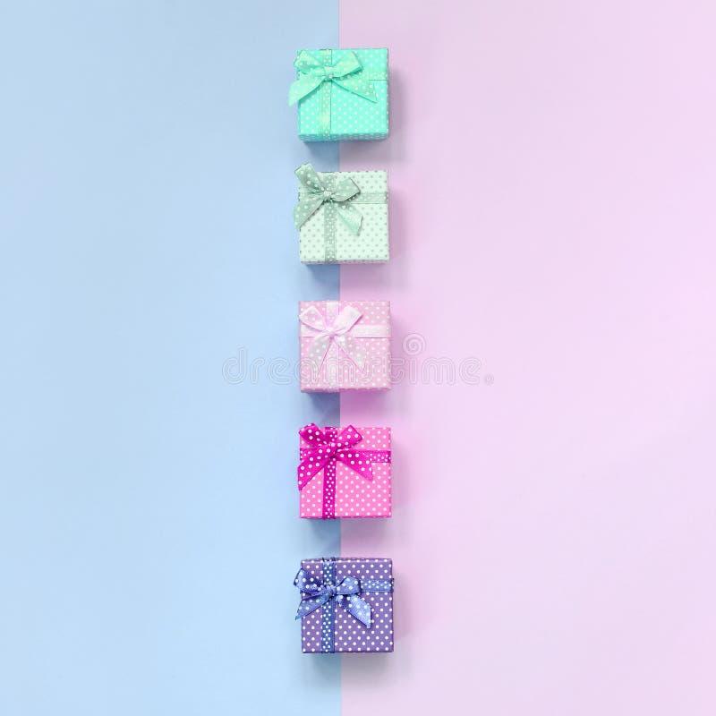 小礼物盒与丝带谎言的不同颜色在紫罗兰色和桃红色背景 免版税图库摄影