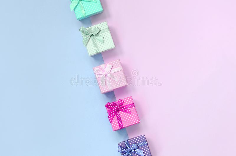 小礼物盒与丝带谎言的不同颜色在紫罗兰色和桃红色背景 免版税库存图片
