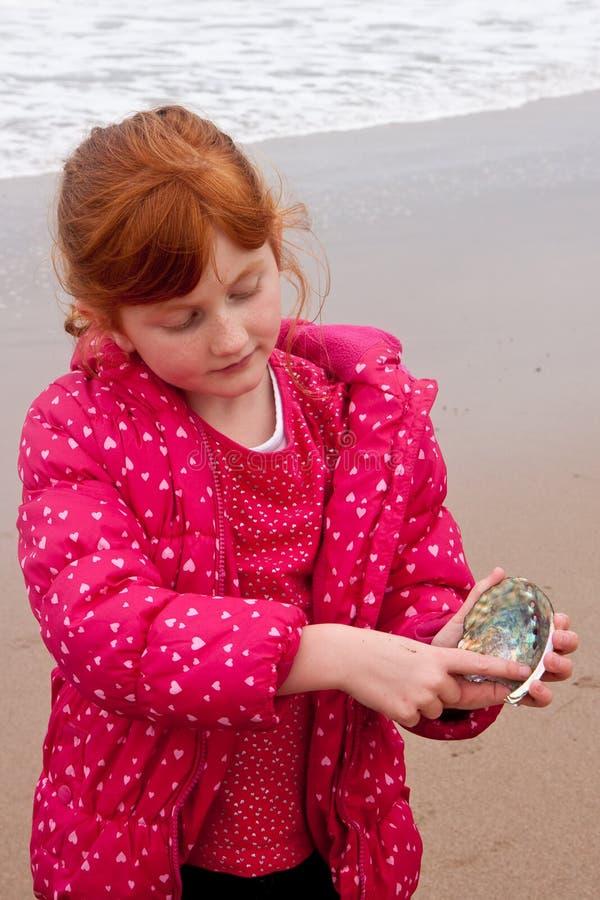 小红发女孩在冬天穿衣在举行paua的海滩 免版税库存图片