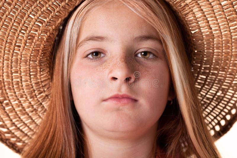 小红发女孩画象有雀斑和草帽的 库存图片