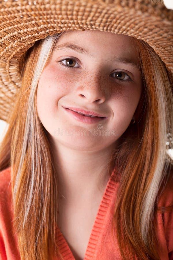 小红发女孩画象有雀斑和草帽的 图库摄影