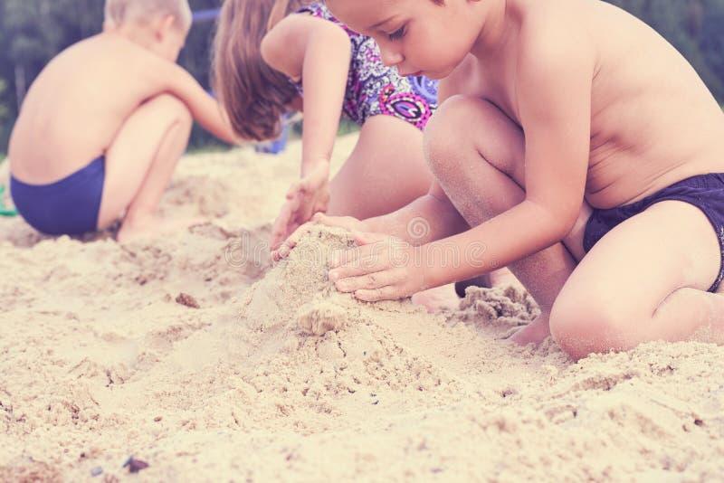 小组一点逗人喜爱的childs做沙子城堡在海滩 库存照片