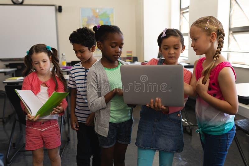 小组一起学习在教室的学校孩子 库存图片