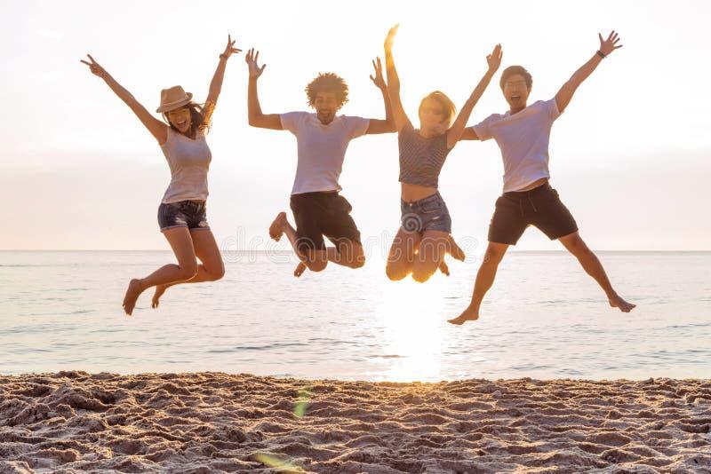 小组一起朋友在获得的海滩乐趣 跳跃在海滩的愉快的青年人 小组朋友享用 库存照片