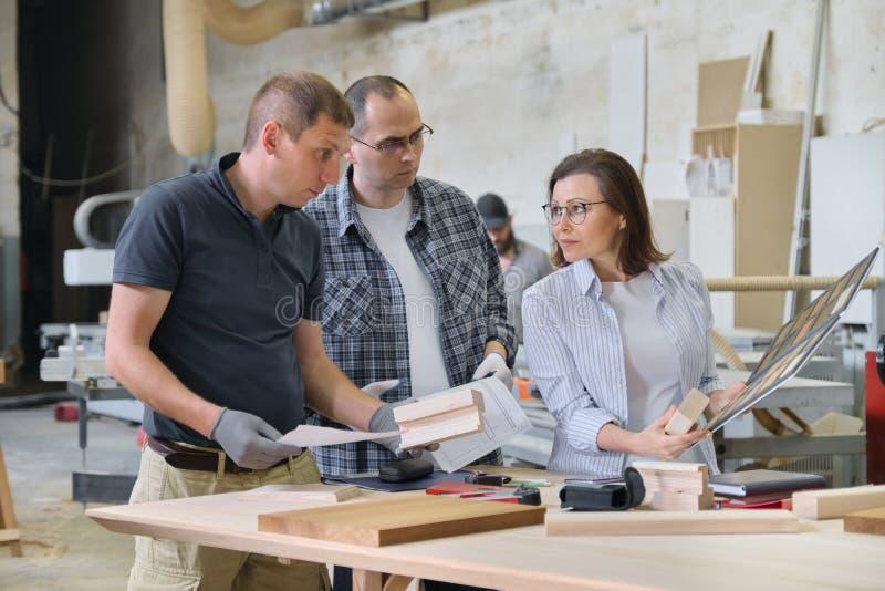 小组一起研究木家具项目的工业人客户、设计师或者工程师和工作者  免版税库存图片