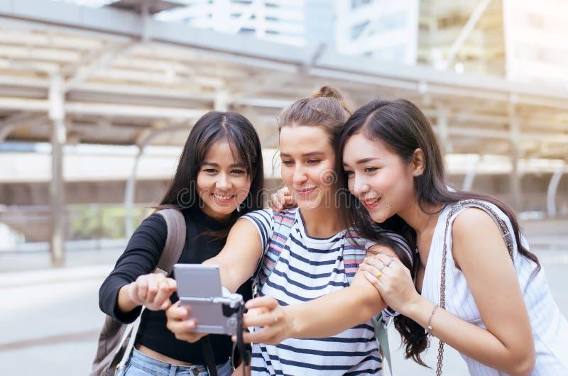 小组不同的妇女旅客在购物中心,美女做她的selfie走在街道,愉快和微笑上 免版税库存图片