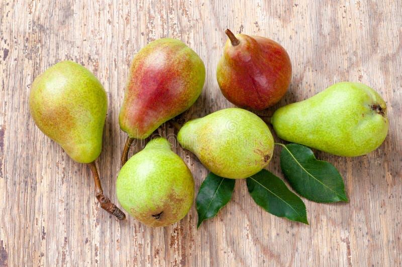 小组与叶子的成熟绿色和红色梨 木深度域浅的表 免版税库存图片
