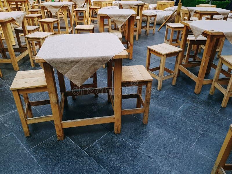 小组与布料盖子和椅子的木表在室外街道食物餐馆 库存照片