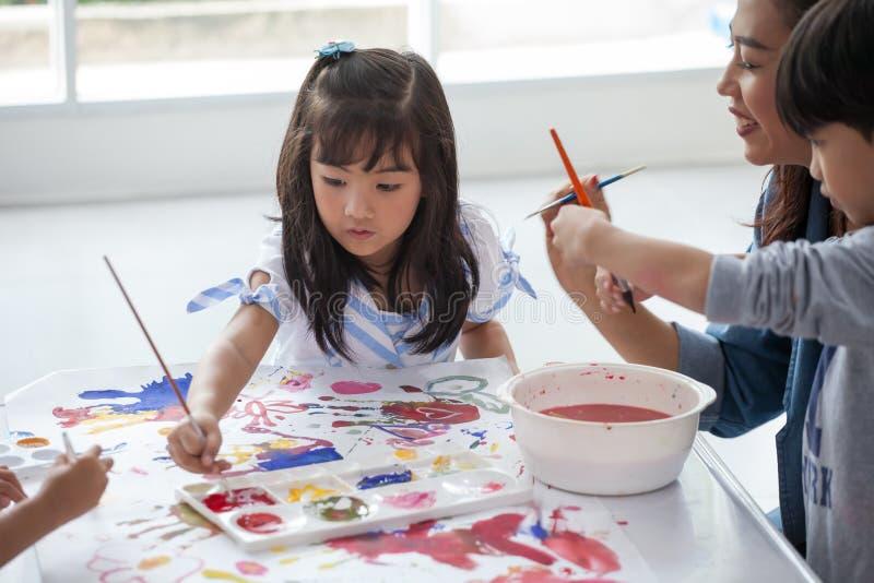 小组与托儿所老师一起的逗人喜爱的女孩女学生绘画在教室学校 愉快的孩子在幼儿园 免版税库存图片