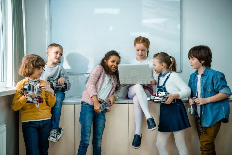 小组与膝上型计算机和机器人的孩子在词根 图库摄影