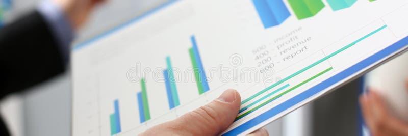 小组与财政图表和银色笔的商人 免版税库存图片