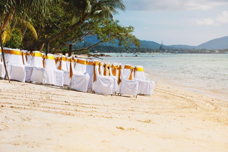 小组与金框格的白色盖子椅子在海滩在婚礼地点准备时 免版税库存照片