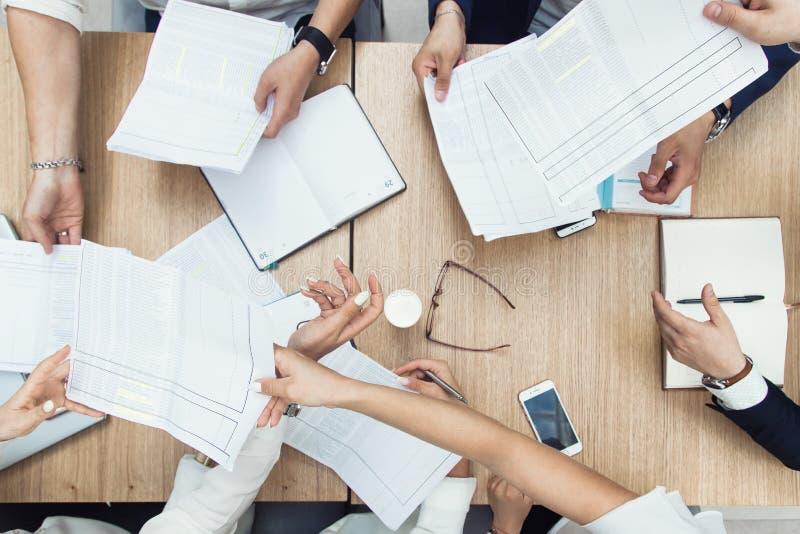 小组业务会议在一起加入业务关系w的现代办公室、团队工作和不同的手的桌上 免版税库存图片
