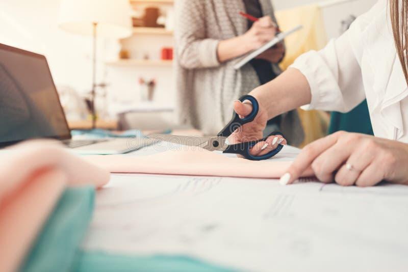 小组两位裁缝工作在缝合的演播室 3d商业查出的小的白色 50mm背景迷离作用射击晚上nikkor当事人端 做创造性的设计礼服的少妇队 免版税库存照片