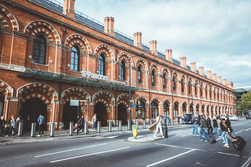 小组乘客或旅客穿过在Cross圣Pancras国王驻地前面的街道 图库摄影