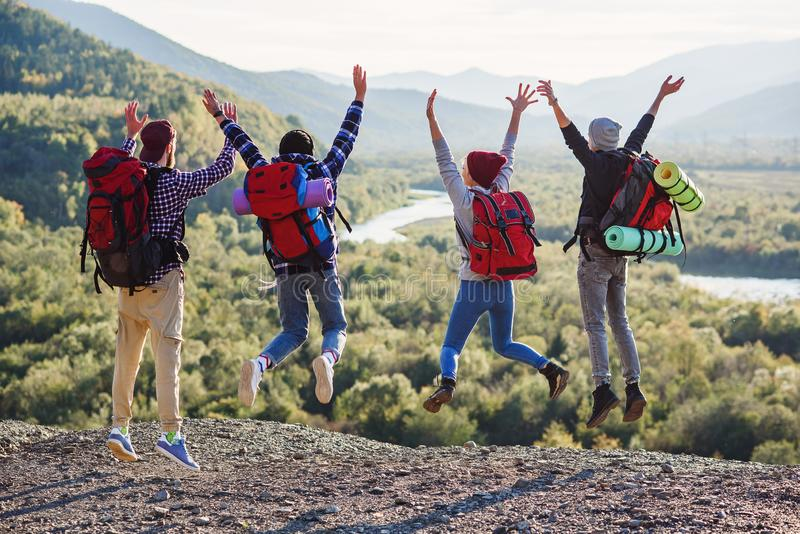 小组五个愉快的朋友跳在背景山的日落时间 库存照片