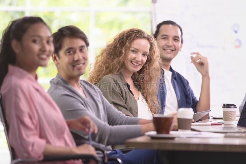 小组亚洲和白种人商人遇见他的工作 E 免版税库存图片