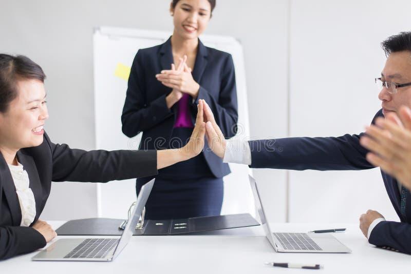 小组亚洲商人拍手在会议以后在屋子,队成功介绍和教练研讨会里在办公室 免版税库存图片