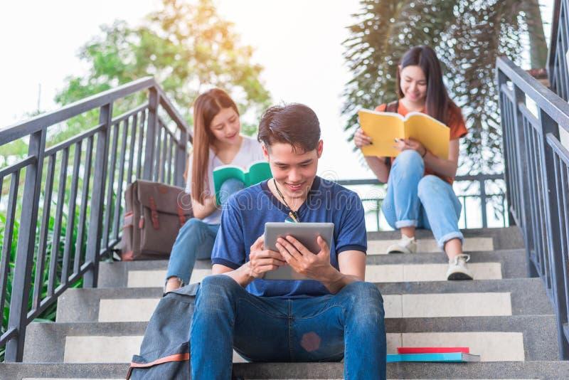 小组亚洲大学生读书和回顾由课本和膝上型计算机在台阶在大学 技术和教育 免版税库存照片
