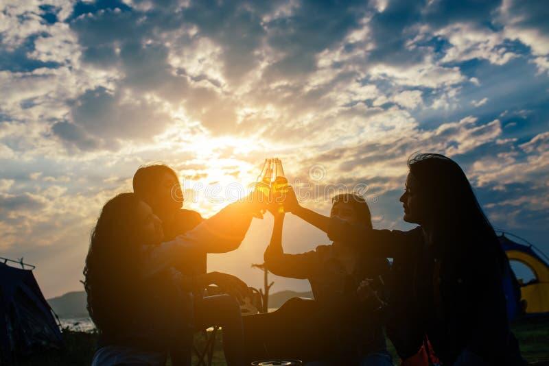 小组亚裔妇女集会与饮料瓶享受旅行野营 库存图片