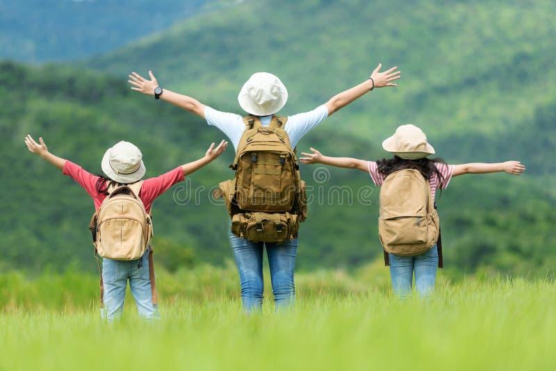 小组亚裔家庭孩子举胳膊,并且身分为目的地看户外、冒险和旅游业和休闲旅行与 免版税库存图片