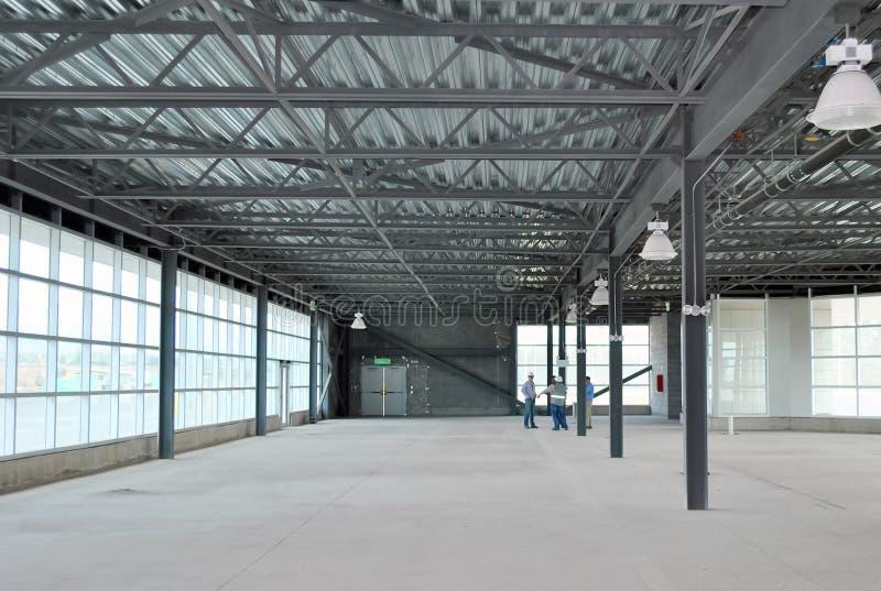 小组会议建造者和建筑师在空的仓库里 免版税库存图片