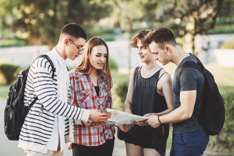 小组使用地图的青年人计划的假期 库存照片