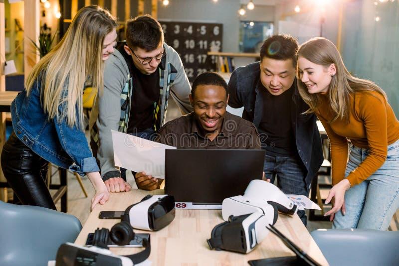 小组使用现代小配件的成人行家工友 四个企业朋友,微笑和打手势,当他们非洲时 免版税库存照片