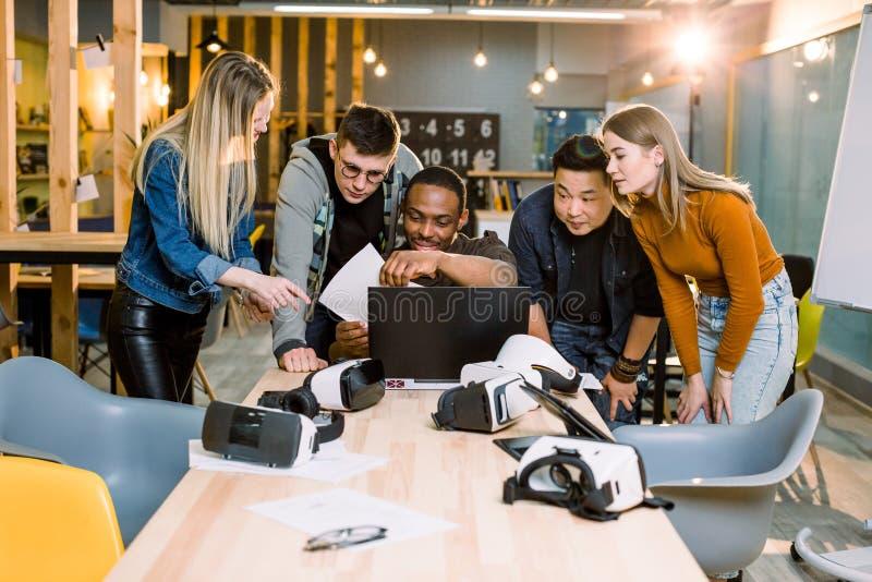 小组使用现代小配件的成人行家工友 四个企业朋友,微笑和打手势,当他们非洲时 库存照片