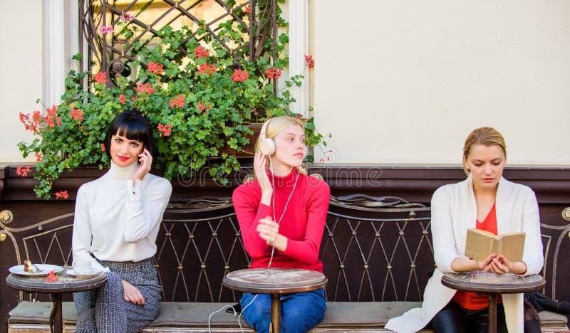小组俏丽的妇女咖啡馆大阳台招待自己与读的讲话和听 信息源 ?? 库存图片